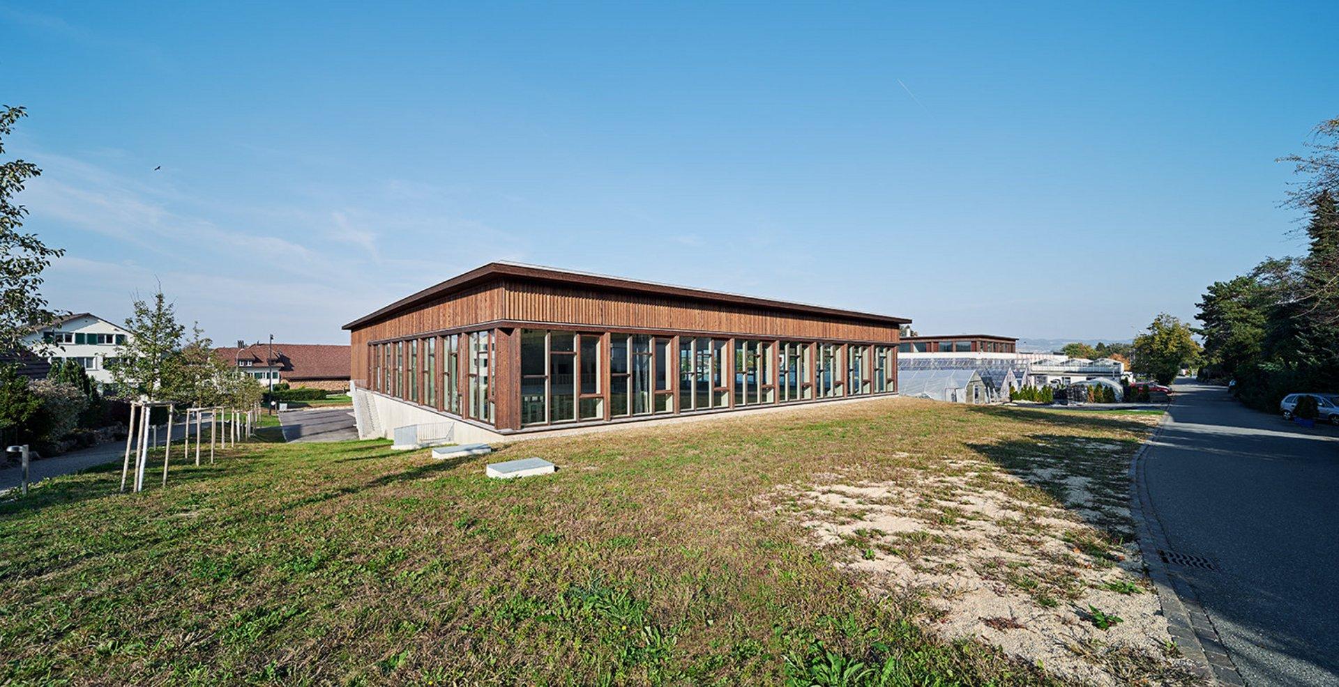 Doppelturnhalle in Elementbauweise und Pfostenriegelsystem mit einer hinterlüfteten Fassade aus druckimprägnierter Weisstannenschalung