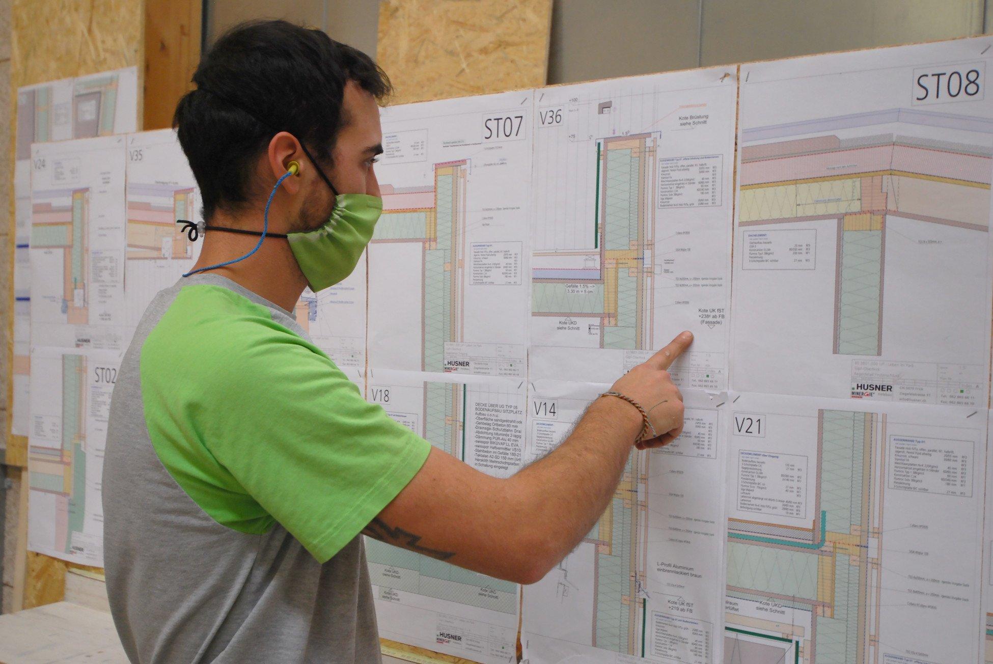 Zimmermann bei HUSNER AG Holzbau liest Plan für die Elementproduktion der Wohnüberbauung Leben im Park in Gipf-Oberfrick in der Werkhalle
