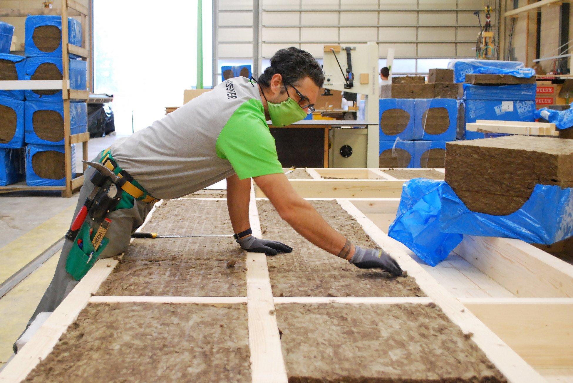 Dämmen der Elemente für die Wohnüberbauung Leben im Park in Gipf-oberfrick in der Werkhalle von HUSNER AG Holzbau