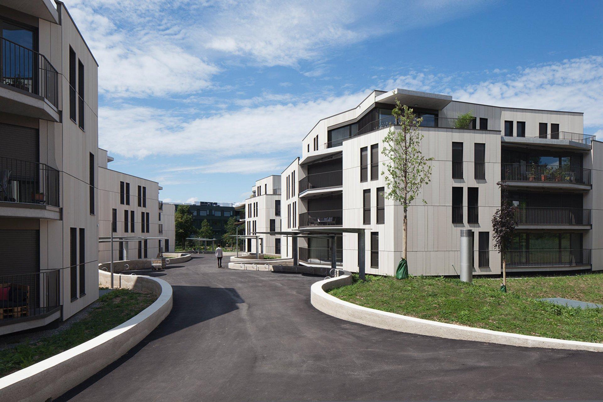 Hinterlüftete Fassade mit einer Bekleidung aus crèmeweissen, unterschiedlich grossformatigen, vertikalen Terracottaplatten.