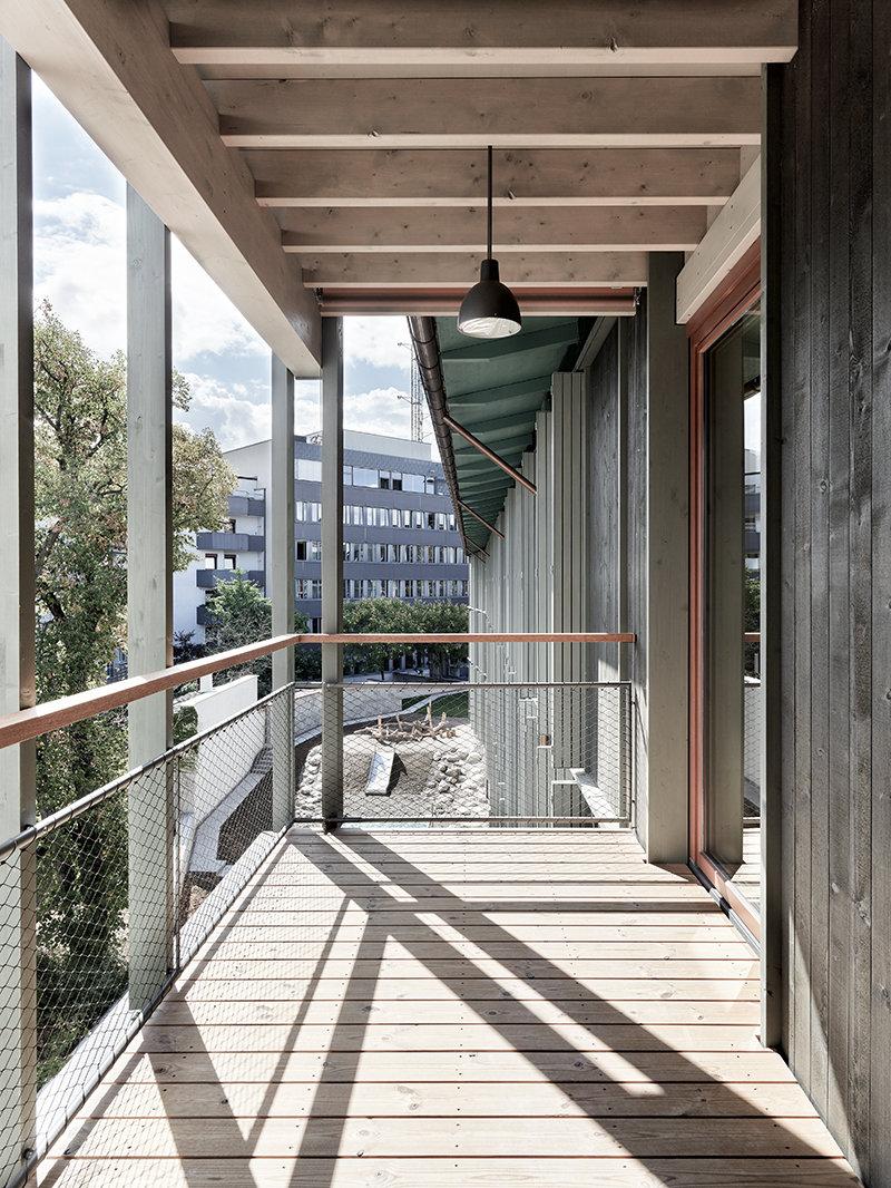 Dreigeschossiger Holzelementbau aus einer hinterlüfteten Fassade aus einer sägerohen, vertikalen, druckimprägnierten Fichtenschalung.