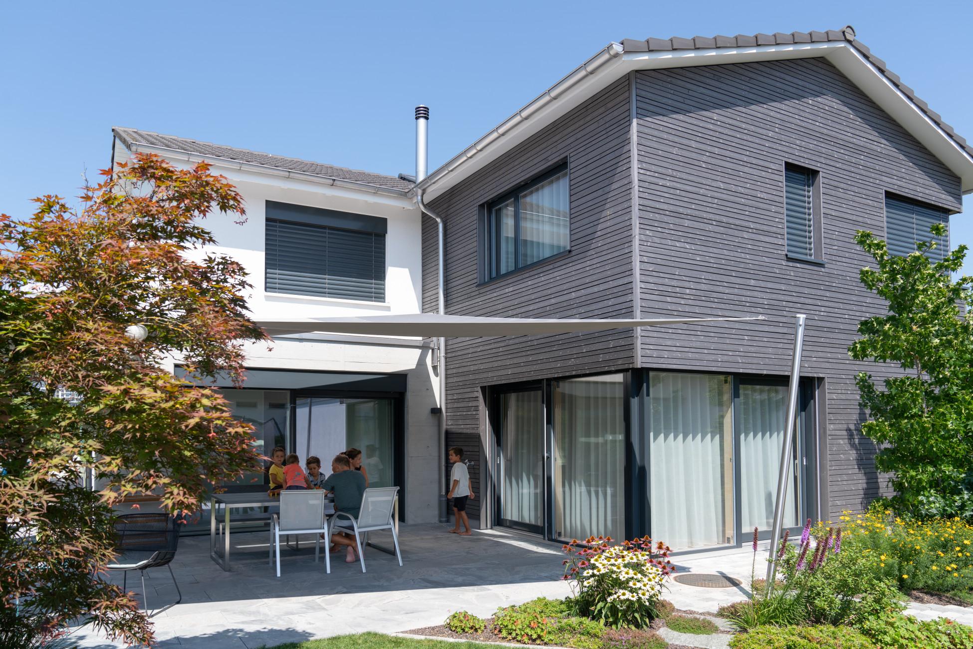 Gesamtleistung Anbau an bestehendes Einfamilienhaus in Holzelementbauweise mit einer vorvergrauten, horizontalen Holzfassade